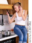 Девушка варит суп и разговаривает по телефону. Стоковое фото, фотограф Николай Михальченко / Фотобанк Лори