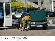 Купить «Мужчина чинит машину на улице», эксклюзивное фото № 2308994, снято 19 сентября 2010 г. (c) lana1501 / Фотобанк Лори