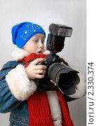 Девочка в зимней одежде удивлённо смотрит на зеркальный фотоаппарат (2011 год). Редакционное фото, фотограф Евгений Волдаев / Фотобанк Лори