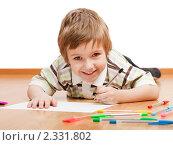 Купить «Улыбающийся мальчик рисует или пишет разноцветными ручками, лежа на полу», фото № 2331802, снято 4 февраля 2011 г. (c) Илья Андриянов / Фотобанк Лори
