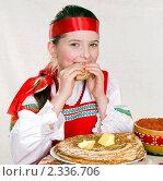 Купить «Девочка в русской национальной одежде ест блины. Масленица.», фото № 2336706, снято 11 февраля 2011 г. (c) RedTC / Фотобанк Лори