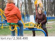 Купить «Счастливая семья. Улыбающаяся женщина качается на качелях с дочерью на детском городке», эксклюзивное фото № 2368490, снято 1 мая 2007 г. (c) Игорь Низов / Фотобанк Лори