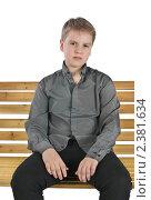 Купить «Серьезный мальчик сидит на лавочке», фото № 2381634, снято 23 ноября 2017 г. (c) Oleg Ivanenko / Фотобанк Лори