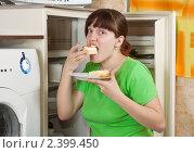 Купить «Девушка ест пирог, открыв холодильник», фото № 2399450, снято 5 марта 2011 г. (c) Яков Филимонов / Фотобанк Лори