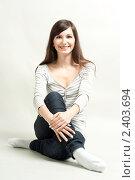 Молодая брюнетка сидит на полу. Стоковое фото, фотограф Черников Роман / Фотобанк Лори