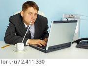 Купить «Очень занятой деловой человек работает на компьютере и пьёт кофе», фото № 2411330, снято 23 ноября 2010 г. (c) pzAxe / Фотобанк Лори