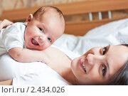 Улыбающийся малыш лежит на груди у матери. Стоковое фото, фотограф Михеев Павел / Фотобанк Лори