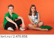 Купить «Мальчик и девочка сидящие на полу. Оранжевый фон», фото № 2470858, снято 12 февраля 2011 г. (c) Oleg Ivanenko / Фотобанк Лори