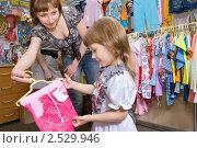 Купить «Продавец  показывает девочке шорты», фото № 2529946, снято 13 мая 2011 г. (c) Типляшина Евгения / Фотобанк Лори