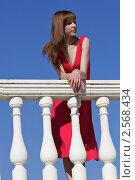 Красивая женщина в красном платье стоит на балконе, облокотившись на балюстраду, на фоне синего неба. Стоковое фото, фотограф Яна Королёва / Фотобанк Лори