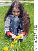 Купить «Девочка сидит на лужайке с желтыми одуванчиками», фото № 2571682, снято 2 июня 2011 г. (c) RedTC / Фотобанк Лори