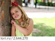 Девочка с красным цветком в волосах стоит у дерева. Стоковое фото, фотограф Елена Сикорская / Фотобанк Лори