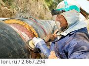 Купить «Рабочий обрабатывает сварной шов на трубе», фото № 2667294, снято 23 июля 2018 г. (c) Дмитрий Калиновский / Фотобанк Лори