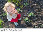 Маленькая девочка сидит на цветочной грядке. Стоковое фото, фотограф Олег Кириллов / Фотобанк Лори