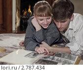 Влюбленные у камина смотрят семейный фотоальбом. Стоковое фото, фотограф Диана Гарифуллина / Фотобанк Лори