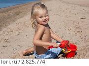 Девочка на пляже в песке с красным совочком и ведерком. Стоковое фото, фотограф Евгения Шийка / Фотобанк Лори