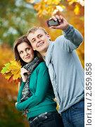 Купить «Влюблённая пара фотографируется в осеннем парке», фото № 2859858, снято 19 февраля 2018 г. (c) Дмитрий Калиновский / Фотобанк Лори