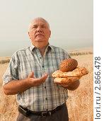 Купить «Пожилой мужчина с хлебом на фоне поля», фото № 2866478, снято 24 июля 2010 г. (c) Дарья Филимонова / Фотобанк Лори