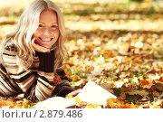 Купить «Улыбающаяся девушка лежит на земле в осеннем парке», фото № 2879486, снято 1 октября 2010 г. (c) Иван Михайлов / Фотобанк Лори