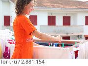 Купить «Женщина развешивает на просушку выстиранное бельё», фото № 2881154, снято 20 июля 2010 г. (c) Losevsky Pavel / Фотобанк Лори