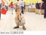 Купить «Уставший мальчик сидит на корточках посреди супермаркета», фото № 2883010, снято 4 июля 2010 г. (c) Losevsky Pavel / Фотобанк Лори