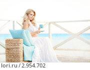 Красивая беременная женщина сидит на веранде коттеджа у моря. Стоковое фото, фотограф Екатерина Штерн / Фотобанк Лори