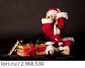 Маленький мальчик в костюме Санта-Клауса сидит на полу схватившись за голову в шоке от подарка. Черный фон. Стоковое фото, фотограф Наташа Чапкайло / Фотобанк Лори