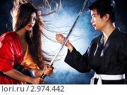 Купить «Молодая японская пара в спортивной одежде с мечом на тёмном фоне», фото № 2974442, снято 1 февраля 2010 г. (c) chaoss / Фотобанк Лори