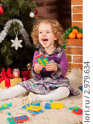 Купить «Маленькая радостная девочка смеется, собирая конструктор, сидя на полу возле новогодней елки», фото № 2979634, снято 19 декабря 2018 г. (c) Ольга Хорькова / Фотобанк Лори