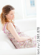 Купить «Красивая беременная женщина сидит на диване», фото № 2981878, снято 24 сентября 2018 г. (c) Ольга Хорькова / Фотобанк Лори