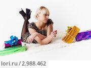 Купить «Лежащая девушка тянет за ленточку, распаковывая подарок», фото № 2988462, снято 13 ноября 2011 г. (c) Александр Фисенко / Фотобанк Лори