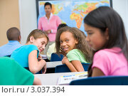 Купить «Две девочки смеются над школьницей на уроке в школе», фото № 3037394, снято 1 марта 2000 г. (c) Monkey Business Images / Фотобанк Лори