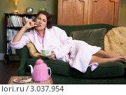 Купить «Женщина отдыхает на диване, ест печенье и пьет чай», фото № 3037954, снято 22 января 2007 г. (c) Monkey Business Images / Фотобанк Лори