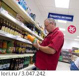 Мужчина выбирает сок в супермаркете (2011 год). Редакционное фото, фотограф Вячеслав Палес / Фотобанк Лори