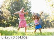 Купить «Девочка с мамой крутят обручи летом на улице», фото № 3054602, снято 3 февраля 2006 г. (c) Monkey Business Images / Фотобанк Лори