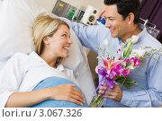 Муж дарит беременной жене в больничной койке цветы. Стоковое фото, фотограф Monkey Business Images / Фотобанк Лори