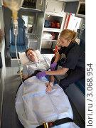 Купить «Медработник с пациентом в машине скорой помощи, оказывает медицинскую помощь», фото № 3068954, снято 6 декабря 2005 г. (c) Monkey Business Images / Фотобанк Лори
