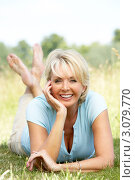 Купить «Радостная зрелая женщина лежит на траве летом», фото № 3079770, снято 24 июня 2009 г. (c) Monkey Business Images / Фотобанк Лори