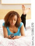 Купить «Девушка лежит на кровати с мобильным телефоном», фото № 3080070, снято 15 апреля 2009 г. (c) Monkey Business Images / Фотобанк Лори