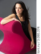 Купить «Молодая привлекательная брюнетка сидит на розовом диване», фото № 3080374, снято 20 апреля 2009 г. (c) Monkey Business Images / Фотобанк Лори
