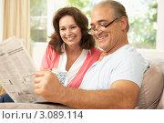 Купить «Портрет мужчины и женщины средних лет на диване с газетой и кружкой чая», фото № 3089114, снято 10 августа 2009 г. (c) Monkey Business Images / Фотобанк Лори