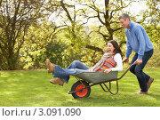 Купить «Счастливая молодая пара, мужчина везет женщину в садовой  тачке», фото № 3091090, снято 17 октября 2009 г. (c) Monkey Business Images / Фотобанк Лори