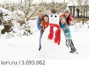 Жизнерадостная семья возле снеговика в зимнем саду. Стоковое фото, фотограф Monkey Business Images / Фотобанк Лори