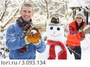 Купить «Улыбающаяся молодая пара лепит снежки возле снеговика в саду», фото № 3093134, снято 3 января 2010 г. (c) Monkey Business Images / Фотобанк Лори