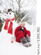 Блондинка пьет чай из термоса, прислонившись спиной к снеговику. Стоковое фото, фотограф Monkey Business Images / Фотобанк Лори