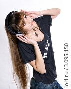 Девушка с длинными русыми волосами слушает музыку в больших наушниках. Стоковое фото, фотограф Павел Сазонов / Фотобанк Лори