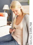Купить «Задумчивая блондинка смотрит на мобильный телефон в руке, сидя дома на ковре», фото № 3095758, снято 18 июня 2019 г. (c) Monkey Business Images / Фотобанк Лори