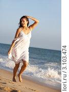 Купить «Счастливая девушка в белом платье гуляет по пляжу», фото № 3103474, снято 1 сентября 2010 г. (c) Monkey Business Images / Фотобанк Лори