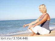 Купить «Улыбающаяся блондинка средних лет сидит в позе лотоса на пляже у берега моря», фото № 3104446, снято 2 сентября 2010 г. (c) Monkey Business Images / Фотобанк Лори