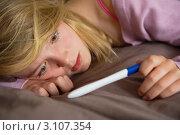 Купить «Мрачная девушка-подросток лежит на диване и смотрит на тест на беременность», фото № 3107354, снято 14 июля 2010 г. (c) Monkey Business Images / Фотобанк Лори